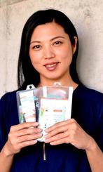 タイで販売する「サンゴに優しい日焼け止め」の試作品を手にするジーエルイーの呉屋由希乃代表