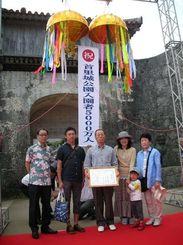 片山所長(左)から5千万人目の認定証を贈られた井上さん(同3人目)=25日、首里城公園歓会門前