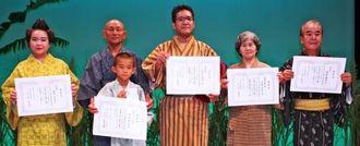 タイムス特別賞の金城さん親子(左から2人目)、最優秀賞の瑞慶山さん(中央)、審査員特別賞の花城さん(右から2人目)ら=名護市民会館