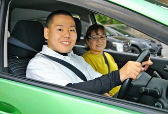 普通自動車免許を取得し、車を運転する照屋樹さん(左)と、母の良江さん=3月22日、北中城村・県立美咲特別支援学校はなさき分校