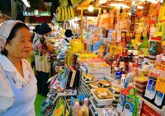 65年前から公設市場で働く喜島ヨシさん(左端)。20年ほど前から、徐々に土産品を取り扱うようになり、今では土産品販売がメーンになっている=21日、那覇市・第一牧志公設市場