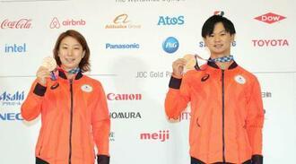 記者会見で記念撮影に応じるバドミントン混合ダブルス銅メダルの渡辺勇大(右)、東野有紗組=31日、東京都内(代表撮影)