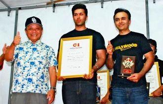 グランプリに選ばれたボリウッドドリームズの(右から)ダスワニ・ダニー社長と息子のダスワニ・ラオー店長、賞状を手渡した野国町長=8日、北谷球場広場