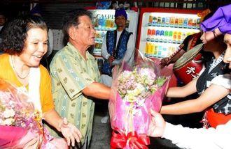 青年会から花束を受け取る城間正子さん(左)と孝吉さん=4日、南城市の大里・大城区