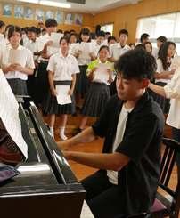 吉見さんの伴奏で合唱する本部高校の生徒=20日、本部高校音楽室