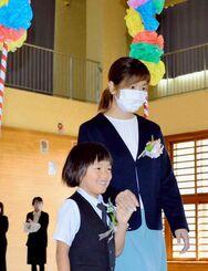 担任と一緒に入場する新入生の荘司八満さん=8日、東村の高江小学校