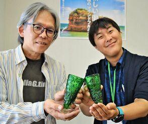 「ゴーヤーグラス」を手にするガラス作家の屋我平尋さん(左)と北中城村観光協会の西田光希さん