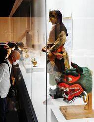 正倉院所蔵の獅子面(右端)や伎楽の人形などに見入る来場者=9日午前、那覇市の県立博物館・美術館(国吉聡志撮影)