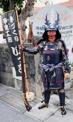 自作の甲冑を着た仲本さん。手にした火縄銃もお手製でクラッカーが飛び出す仕掛け=北谷町浜川