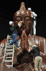 沖縄平和祈念像のほこりを拭き取る県工芸振興センターの職員ら=21日午後、糸満市摩文仁・沖縄平和祈念堂