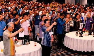 沖縄タイムスの創刊70周年を祝い乾杯する武富和彦社長(手前中央)、豊平良孝会長(同左)ら=20日、ANAクラウンプラザホテル沖縄ハーバービュー