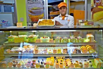 イメージカラーのオレンジの帽子姿で商品を手にする店主の當間学さん=豊見城市宜保