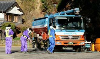 宮崎県日向市で、畜産関係者の車両を消毒する作業員ら=1日午前8時19分