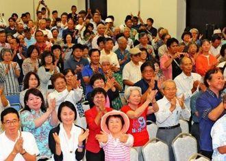 登壇した沖縄2紙の代表者に拍手でエールを送る参加者=4日午後、那覇市の県市町村自治会館