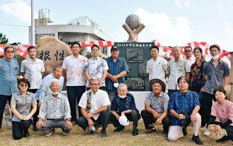 区民らと記念碑の完成を祝う我如古盛次さん(後列右から7人目)、銘苅圭介さん(同8人目)=1日、名護市・久志区野外運動場