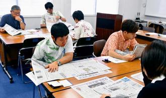 真剣な表情で新聞を読む受講者=南風原町・光文堂コミュニケーションズ本社