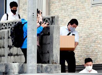 家宅捜査が行われた容疑者宅からダンボールを運び出す捜査員=13日午後4時41分、那覇市内(画像の一部を加工しています)