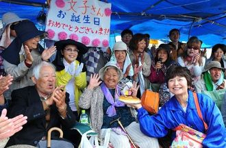 名護市辺野古新基地建設を抗議行動を続ける島袋文子さん(中央)の86歳の誕生日を祝う市民ら=10日午前、キャンプ・シュワブ前