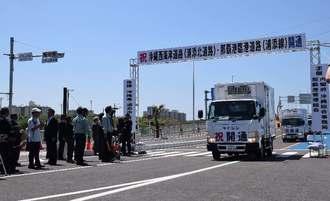 臨港道路浦添線と浦添北道路の開通を祝い、通り初めをする関係者=18日正午すぎ、浦添市港川