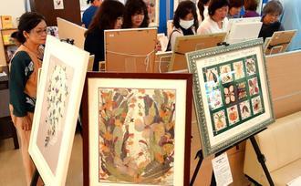 色鮮やかな押し花やレカンフラワーが並んだ故當間光江さんの作品展=16日、糸満市・南部病院1階ロビー