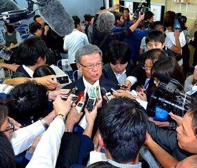 当選確実を受け、殺到する記者団に囲まれて質問に答える翁長氏=16日夜、那覇市