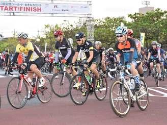 一斉にスタートする「沖縄本島一周サイクリング」の参加者たち=10日午前7時すぎ、名護市21世紀の森体育館前