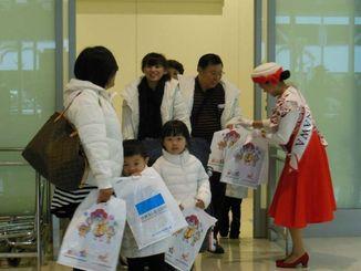 華信航空の定期便初便で台湾の高雄から到着した乗客にミス沖縄から観光ガイドなどが配られた=4日、那覇空港国際線ターミナル