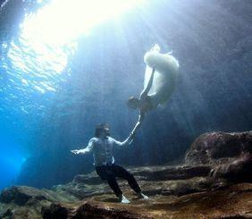 まばゆい光が差し込む中、海中ウエディングを挙げた後藤毅さんと美紀さん(長谷和典さん提供)