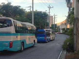 団体客を迎えるために路上で待機する貸し切りバス=12日午後5時40分ごろ、那覇市の牧志公園前