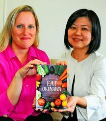 沖縄の食材とレシピを英語で紹介するガイドブックを製作したケイシー・アニスさん(左)と宇栄原千春さん=沖縄タイムス社