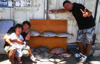 安謝海岸で63センチ、4・12キロのアカナーなどを釣った海武者シーブサーの石原秀樹さん(右)さんと上原隼人さん=8月28日
