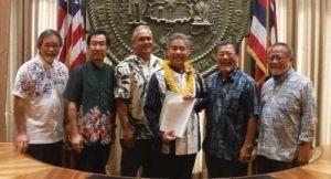 翁長知事からの祝辞をイゲハワイ州知事(右から3人目)に手渡す呉屋会長(同2人目)。(左から)タサトさん、東会長、マッカートニー知事顧問、右端は仲宗根さん=15日、ハワイ州庁舎