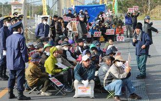 資材などの搬入を阻止しようと、新ゲート前で座り込む反対住民=19日午前9時24分、名護市辺野古のキャンプ・シュワブ