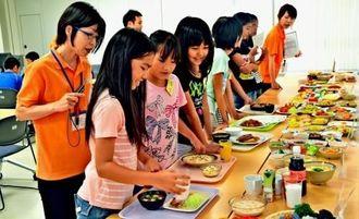 普段の食事をフードモデルで再現する子どもたち=18日、西原町保健センター