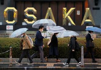 大阪市役所前をマスク姿で歩く人たち=6日午後6時15分