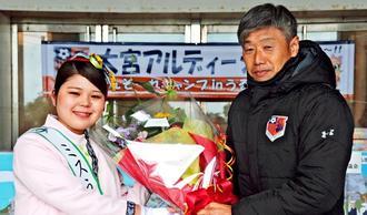 ミスうるまの又吉ひかるさんから花束を受け取る大宮の高木琢也監督(右)=うるま市具志川運動公園