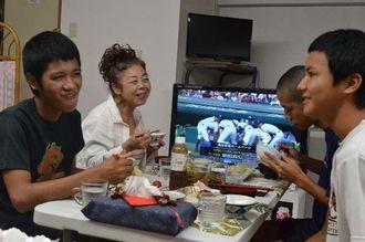 大家の新垣さん(左から2人目)を囲み、昼食をとる沖縄工業高の生徒たち=14日、那覇市繁多川