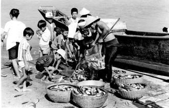 大漁のガチュンに群がる子どもたち=1977年、南城市玉城・奥武(中村一男さん撮影)