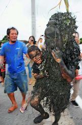 集落内で人々に泥を塗りたくるパーントゥ=11日午後、宮古島市平良島尻(新垣亮撮影)