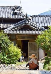 倒壊した家屋を前に作業の手を止める住民=15日午後2時10分ごろ、熊本県益城町