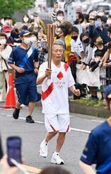 長崎県長与町を走る聖火ランナーの栗山秋義さん=8日午前