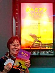 これまでに鑑賞した映画チケットを手に笑顔を見せる久高純子さん=9日、北谷町・ミハマ7プレックス