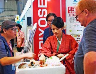 出展商品について質問する香港人ブロガー(左)ら=28日、宜野湾市・沖縄コンベンションセンター