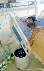 NPO法人アジアチャイルドサポートが酸素濃縮器(中央下)を寄贈した病院で吸入を受ける新型コロナウイルス感染症の患者=5月14日、インドのイーストデリー(同法人提供)