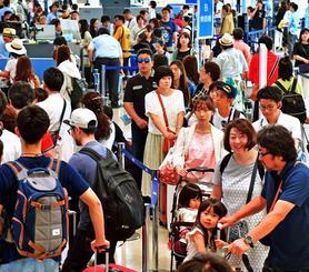 搭乗手続きに並ぶ観光客で混雑する那覇空港出発ロビー=5日