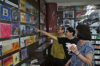 備瀬善勝館長(左)から沖縄市音楽資料館「おんがく村」に展示されているレコードの説明を受ける来館者=12日、沖縄市中央の同館