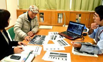 うるま市教育委員会が所蔵する写真を確認する平敷屋エイサー保存会の東武事務局長(左から2人目)=1月29日、うるまし市与那城の海の駅あやはし館