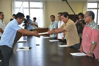 中嶋浩一郎局長(左)に抗議文を手渡す桑江朝千夫沖縄市長(右から2番目)=13日午前、沖縄防衛局