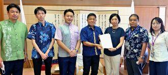 赤嶺昇議長(左から4人目)へ支援を求める陳情書を手渡す中国東方航空の我謝生里氏(同5人目)ら=12日、県議会