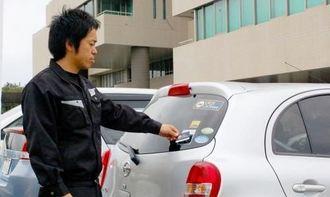 ICカードをセンサー部分にかざし乗車手続きをする利用者=那覇市・沖縄産業支援センター駐車場内のステーション